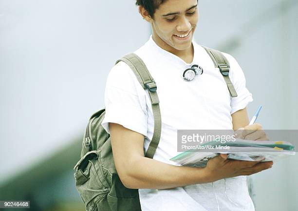 male student standing and writing on folder - strap stock pictures, royalty-free photos & images