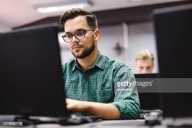 male student studying over laptop at computer lab. - distance learning stock pictures, royalty-free photos & images
