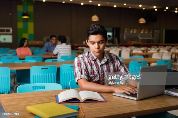 男子学生が本からコンピューターに入力