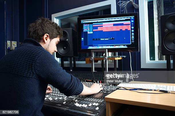 Male student using sound mixing equipment in college music booth