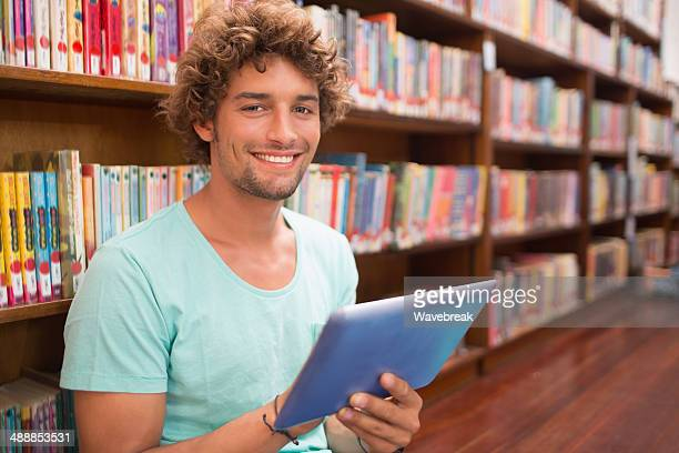 Male student using tablet PC in library