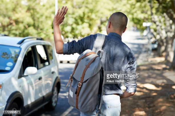 male student waving while waiting on roadside - waving gesture stock pictures, royalty-free photos & images