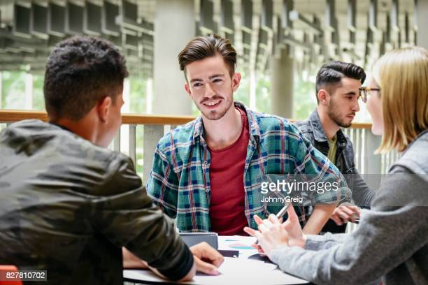 Male student wearing checked shirt sitting in common room with two college freinds