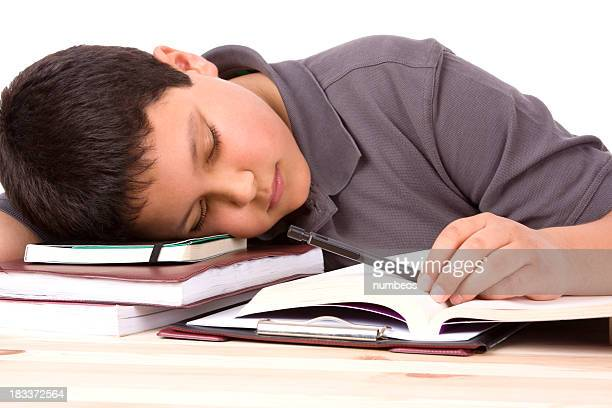 A male student with his head resting on his books sleeping