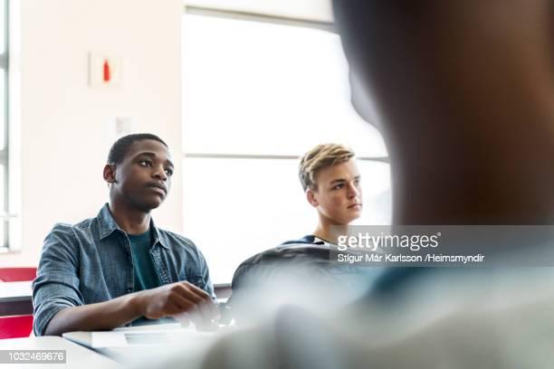 mannelijke studenten luisteren in klas - alleen tieners stockfoto's en -beelden