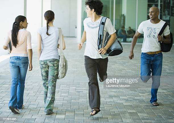 male students running across campus, looking back at female students - moving past stock photos and pictures
