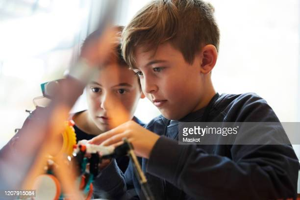 male students working with robot for science project in classroom - enfoque diferencial fotografías e imágenes de stock