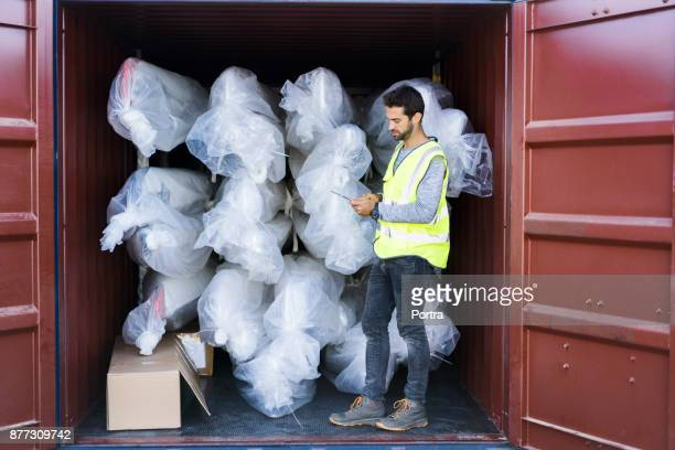 Male supervisor examining stock in cargo container