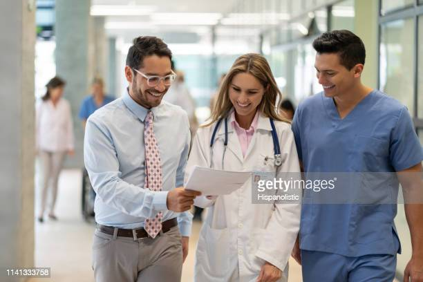 superviseur masculin d'un hôpital montrant quelques papiers à la femme médecin et infirmière tout en marchant dans le couloir tout souriant - down blouse photos et images de collection