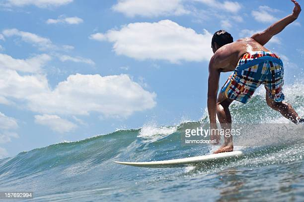 A male surfer bending down to ride a wave