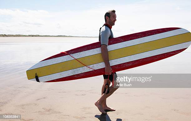 Male Surfer carrying board on beach