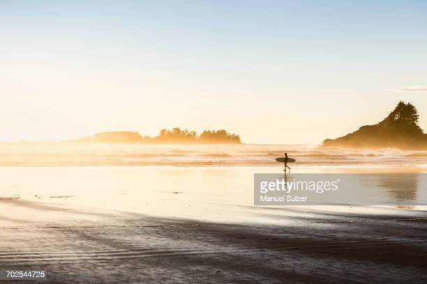 male surfer carrying surfboard on long beach, pacific rim national park, vancouver island, british columbia, canada - vancouver island stockfoto's en -beelden