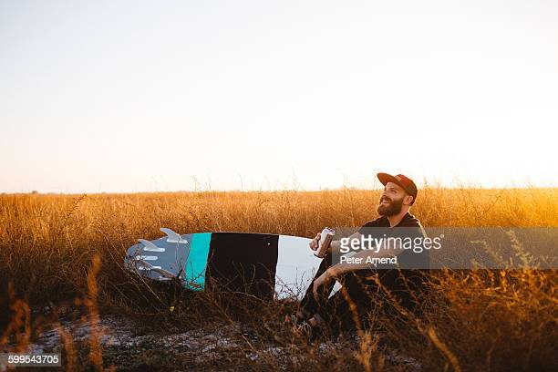 Male surfer drinking beer in field of long grass at sunset, San Luis Obispo, California, USA