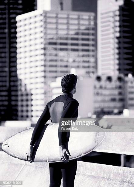 Male surfer looking at cityscape (B&W)