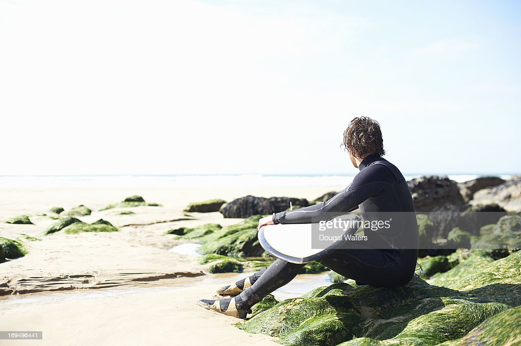 Male surfer looking out toward sea. : Bildbanksbilder