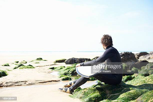 Male surfer looking out toward sea.