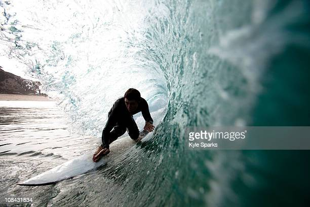 a male surfer navigates the barrel while surfing at westward in malibu, california. - malibu stock pictures, royalty-free photos & images