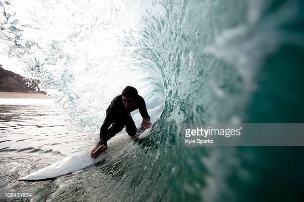 a male surfer navigates the barrel while surfing at westward in malibu, california. - surfer stock-fotos und bilder