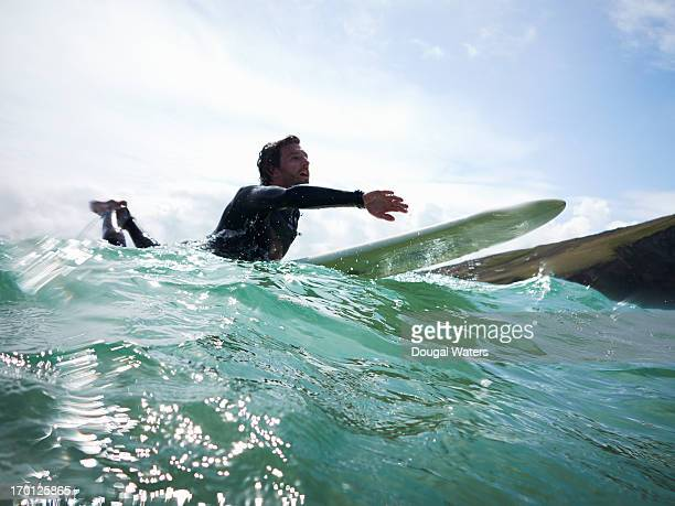 Male surfer on board in sea.
