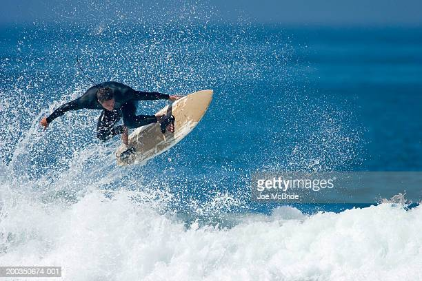 male surfer performing aerial manoeuver above wave - termine sportivo foto e immagini stock