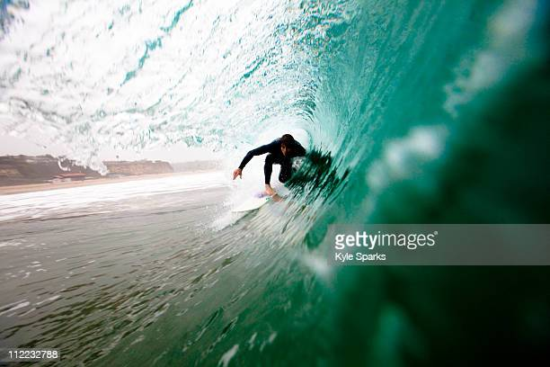 a male surfer pulls into a barrel while surfing at zuma beach in malibu, california. - zuma beach stock photos and pictures
