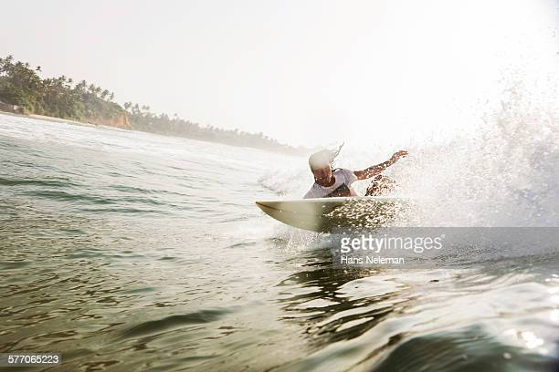 Male surfer riding wave, view from water