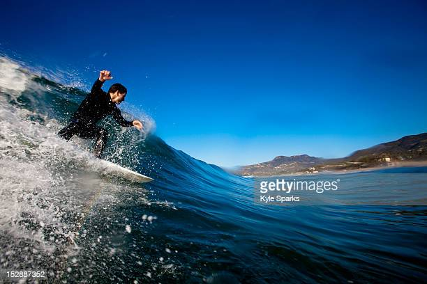 a male surfer sets up for a backside barrel while surfing at zuma beach in malibu, california. - zuma beach stock photos and pictures