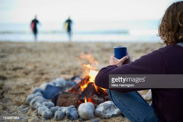 male surfer sitting by fire at beach party. - só homens de idade mediana - fotografias e filmes do acervo