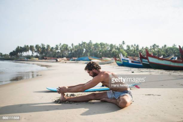 Male surfer stretching on the beach
