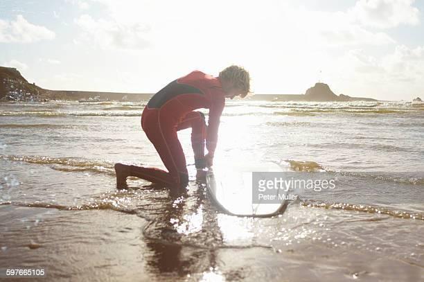 Male surfer untying surfboard from ankle