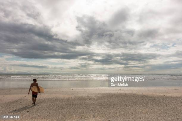 Male surfer walks out to the beach break at Playa Santa Teresa in Malpais on the Nicoya Peninsula on the 9th November 2016 in Costa Rica, Central...