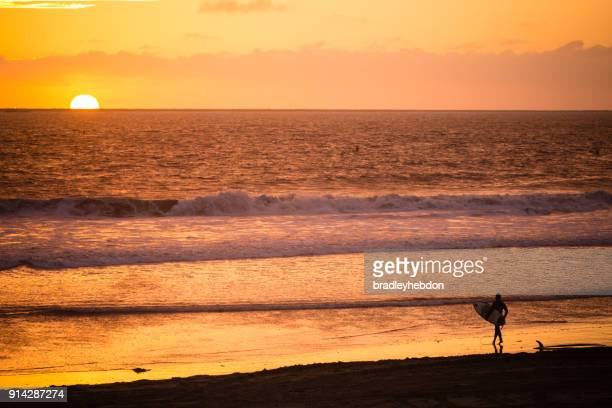 male surfer watching sunset on the shores of seal beach, ca - seal beach stock pictures, royalty-free photos & images