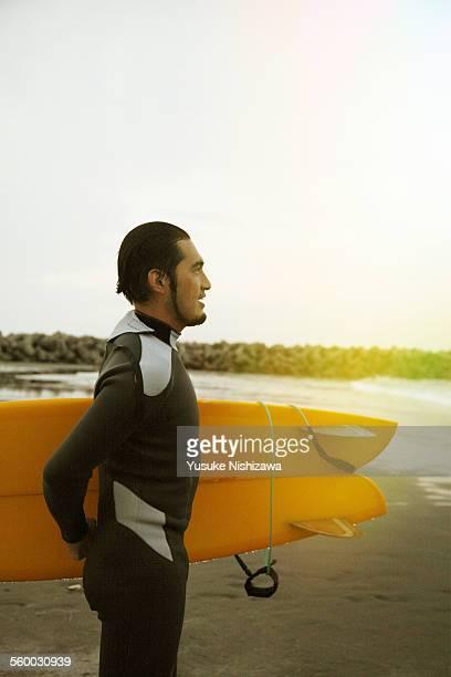 male surfer with morning sun shine - yusuke nishizawa stock-fotos und bilder