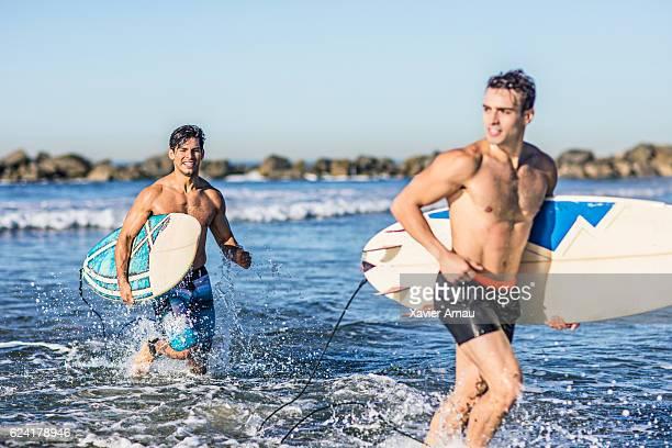 Male surfers running in sea water