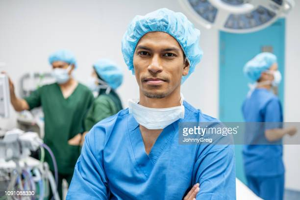 male surgeon in his 30s looking at camera with serious expression - surgeon stock pictures, royalty-free photos & images