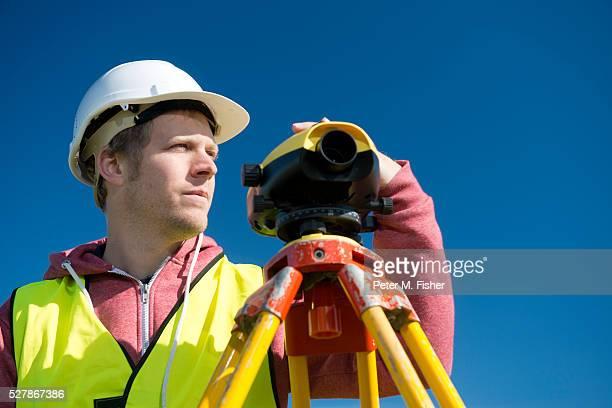 male surveyor using theodolite - inspetora - fotografias e filmes do acervo