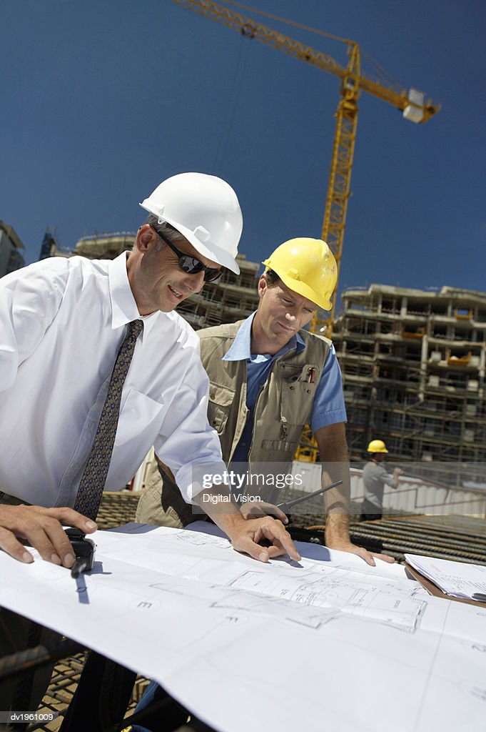 Male Surveyors Wearing Hard Hats in a Building Site Discuss a Blueprint : Stock Photo