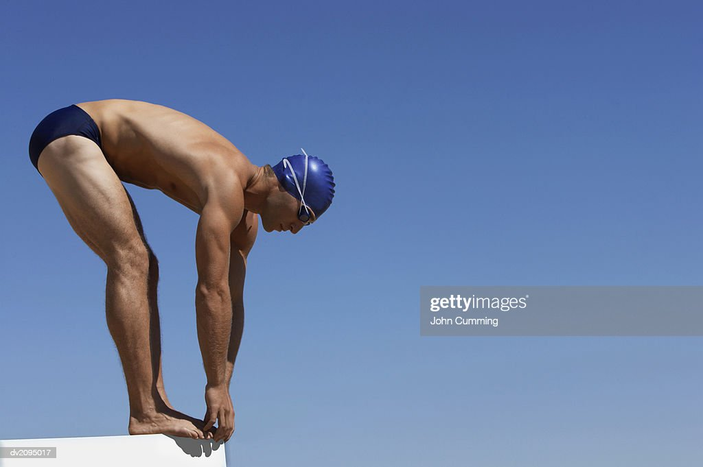 Male Swimmer About to Dive Into a Swimming Pool : Stock Photo