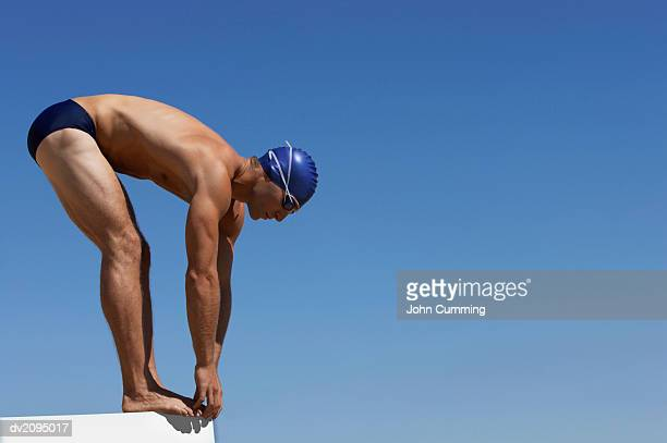 male swimmer about to dive into a swimming pool - young men in speedos stock pictures, royalty-free photos & images