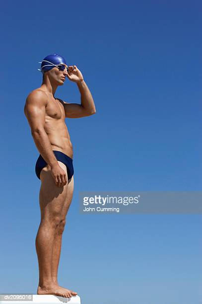 male swimmer adjusting his swimming goggles - man wearing speedo stock photos and pictures