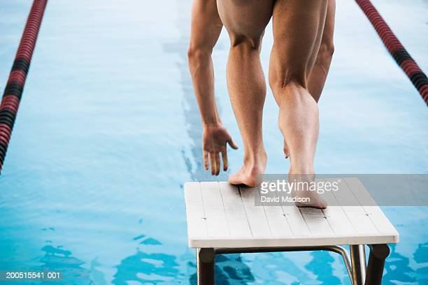 Male swimmer on starting block, low section, rear view