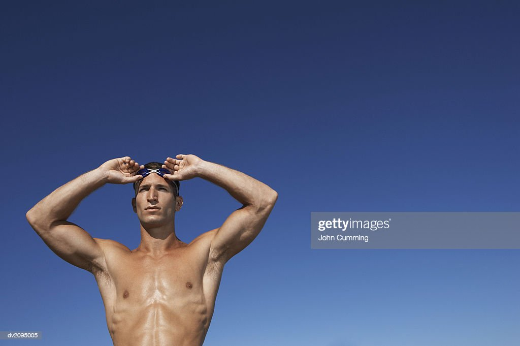 Male Swimmer Putting on His Goggles : Stock Photo