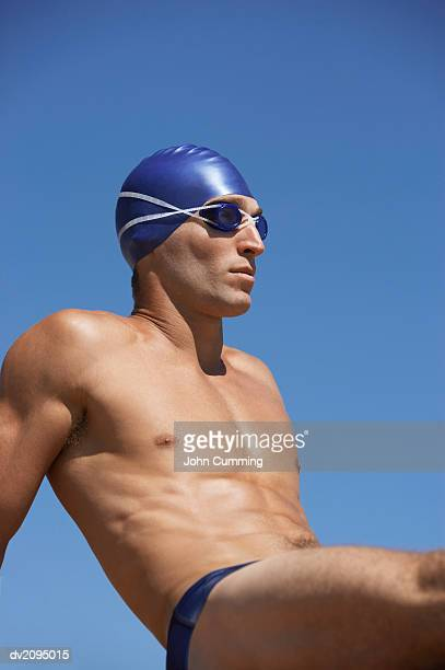 male swimmer sitting down - young men in speedos stock photos and pictures