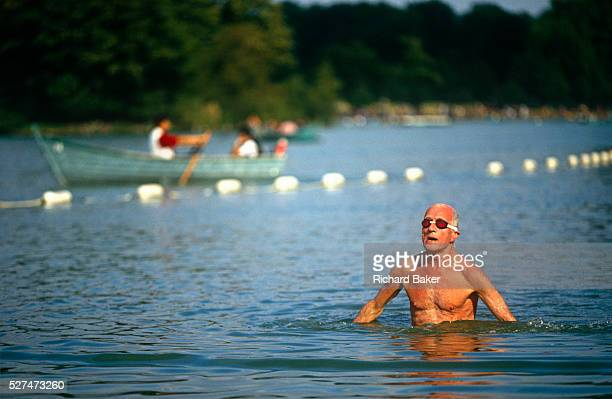 A male swimmer stands up after doing the Crawl across this scene of fresh water bathing in the Serpentine Lake in London's Hyde Park This bathing...