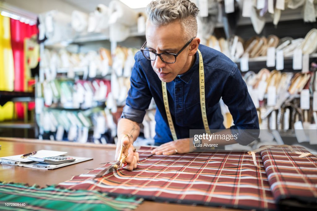 Male tailor cutting a textile at workbench : Stock-Foto
