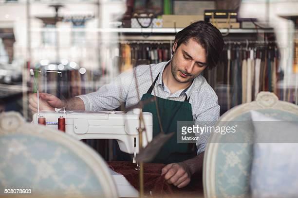 Male tailor working in design studio