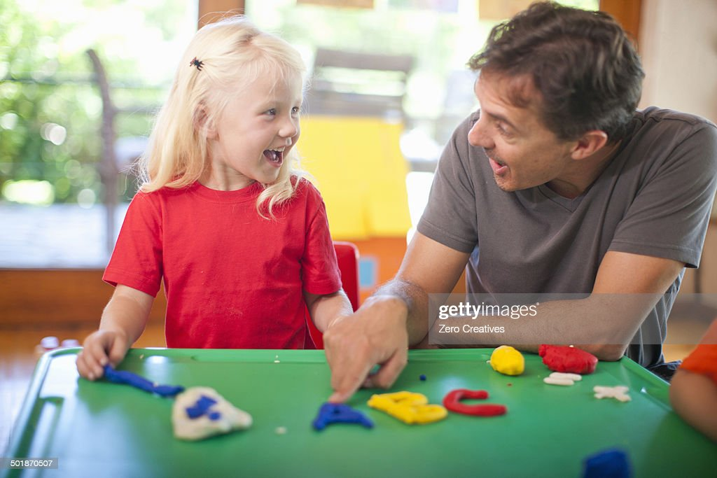 Male teacher and girl learning alphabet at nursery school : Stock Photo