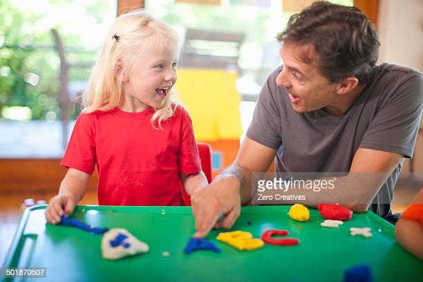 Male teacher and girl learning alphabet at nursery school