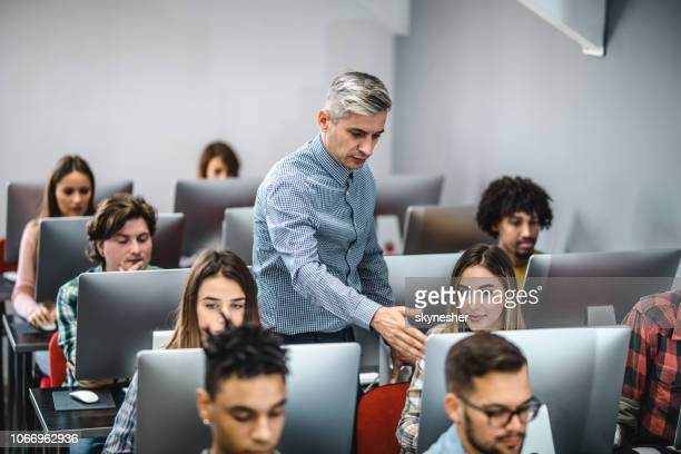male teacher assisting his students on a computer class. - lecturer stock pictures, royalty-free photos & images