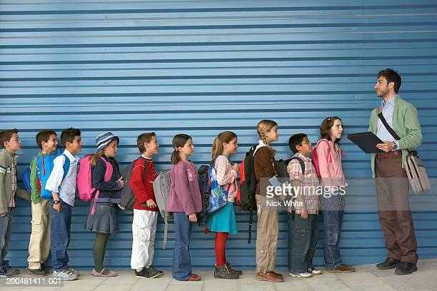 male teacher by row of children (8-12), side view - in a row stock pictures, royalty-free photos & images